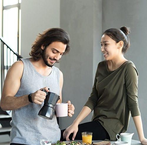 リビングでコーヒーを飲みながら話をしているカップル