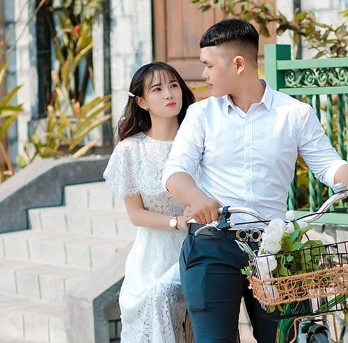 自転車に2人乗りしているカップル