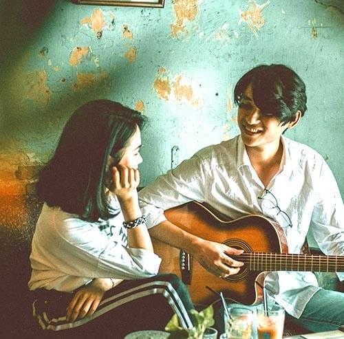 ギターの演奏を女性に聞いてもらっている男性