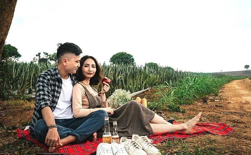 畑で座ってお酒を飲んでいるカップル