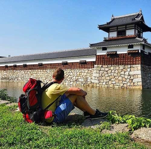 座って城壁を眺める観光客