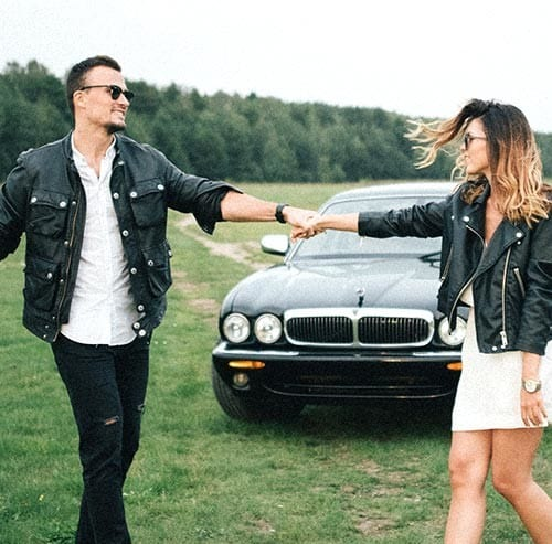 車の前で手を繋いでいるカップル