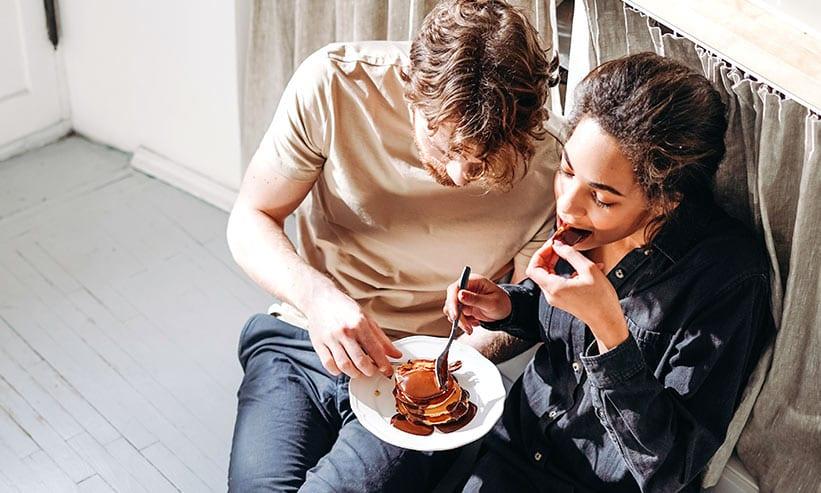 足を伸ばして座りながらパンケーキを食べるカップル