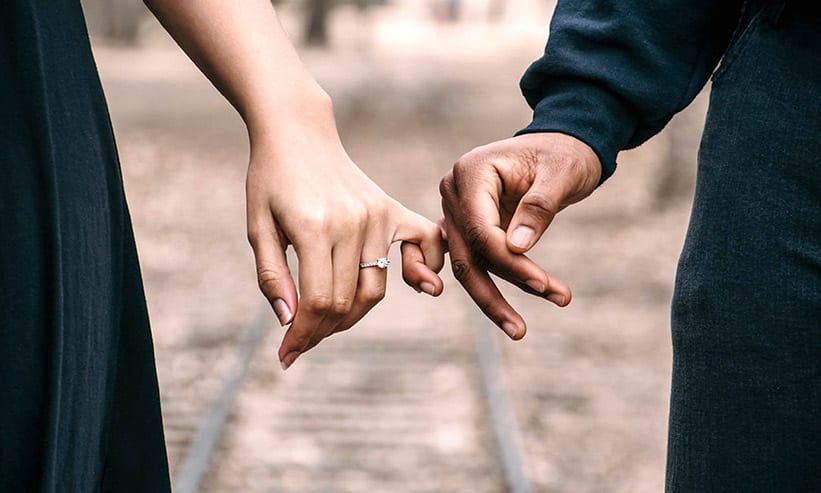 小指と小指を繋いでいるカップル