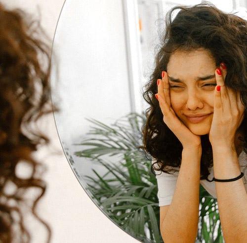 鏡の前で頬に両手をあてて変顔をしている女性