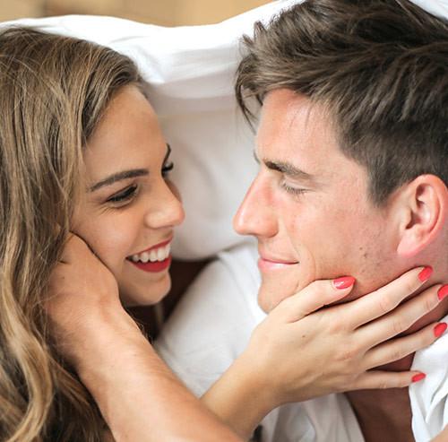 寝転んでお互いの頬に手を置くカップル