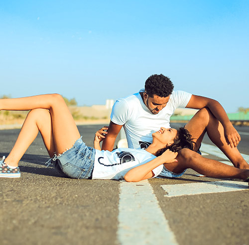 道路に寝転び男性の足に頭を置く女性