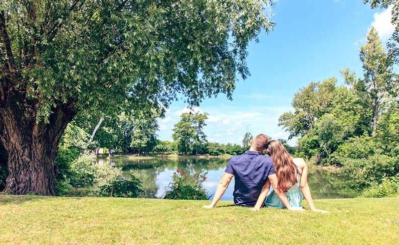 湖のほとりで頭を寄せて座るカップルの後ろ姿