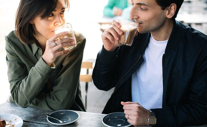 カフェで見つめあいながらコーヒーを飲むカップル